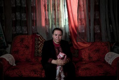 Ektmal Hamd, responsable manager for the Union of Palestinian Women's Committees for The Great March of Return, is posing holding a Kofia in her living room. She is not married and she doesn't have children that's very rare between palestinian women.