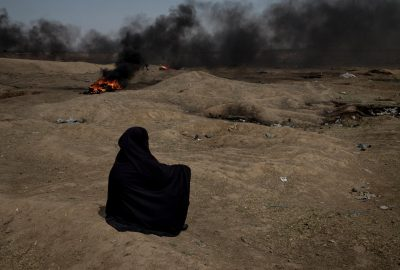 South Gaza. A woman is seen sitting in front of the border with israel during the protests for The Great March of Return.